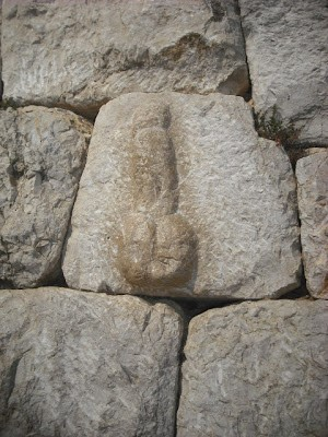 A phallus by the gate of the wall, symbol of prosperity and luck
